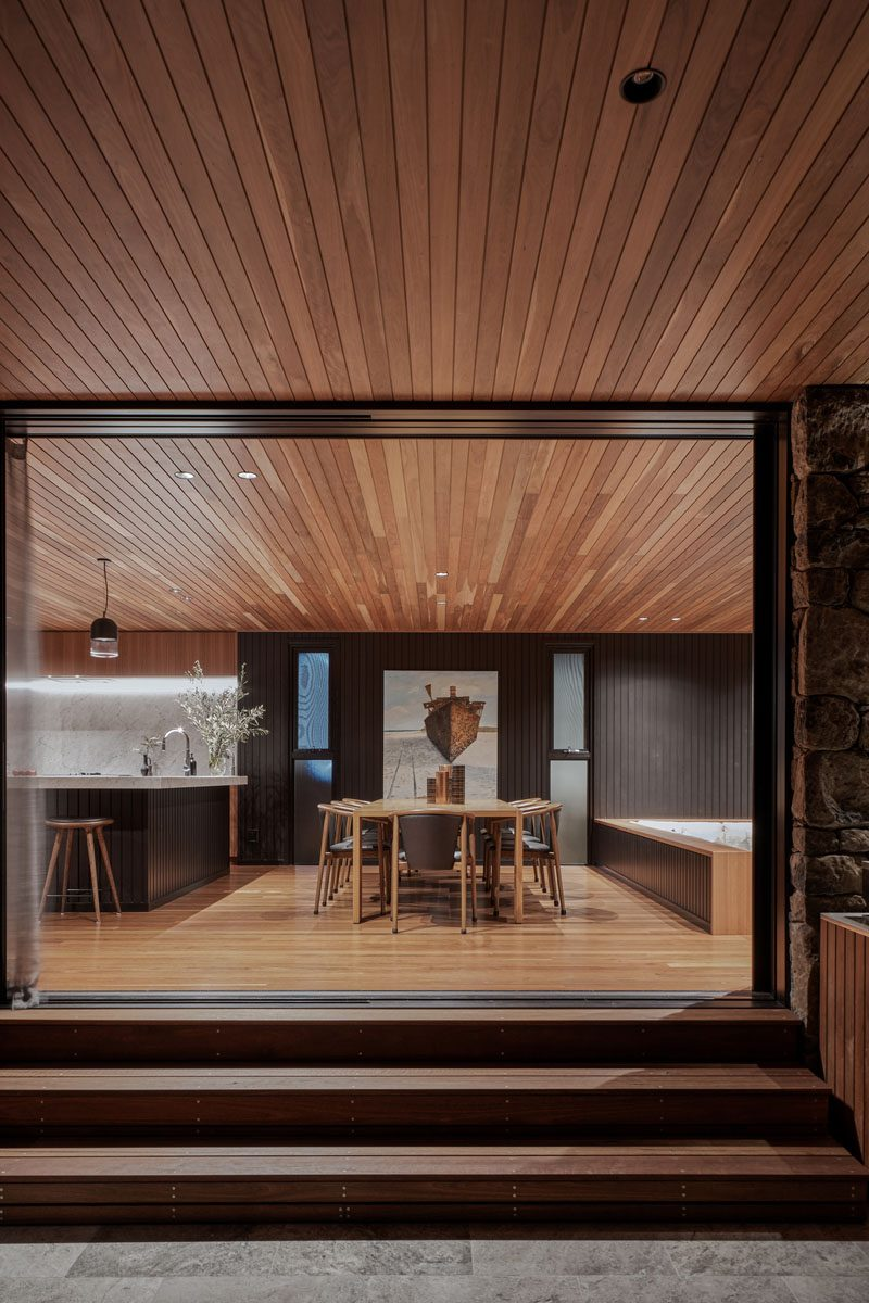 Separating the kitchen and the living room of this modern house, is the dining area. The wood ceiling seamlessly flows from the interior to the exterior spaces. #ModernDiningRoom #DiningRoomIdeas #WoodCeiling