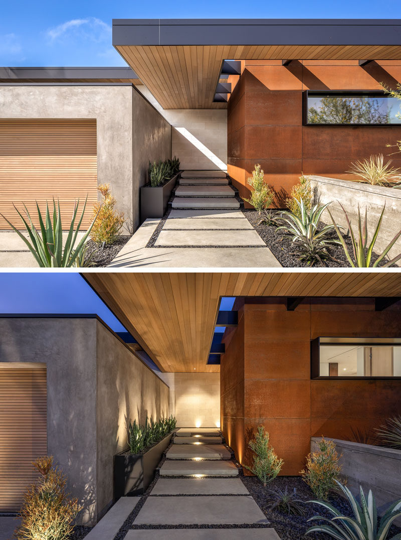 Architecture Ideas - The facade of this modern house features a weathered steel accent, and plants that line the walkways. At night, the entrance is lit up with hidden lighting elements. #ModernHouse #ModernArchtiecture #ModernLandscaping #LandscapingIdeas