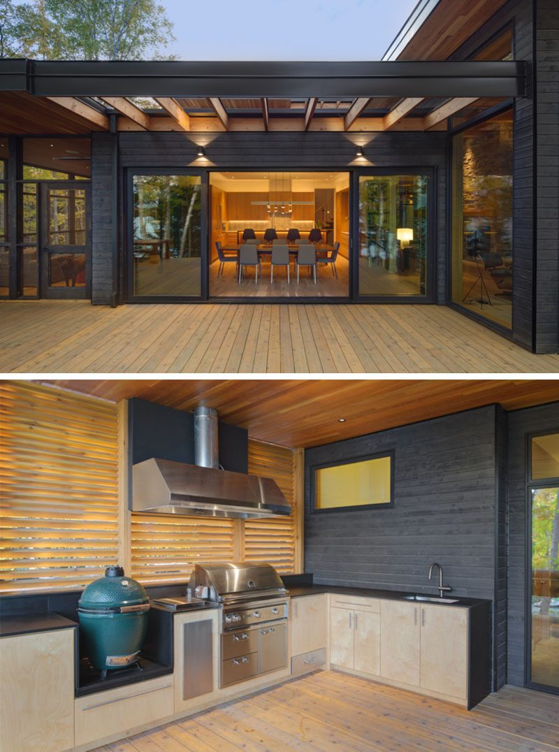 This modern house has an outdoor kitchen with a built-in grill and smoker, that's is adjacent to a screened porch, and is protected by a roof and privacy screen. #OutdoorKitchen #ModernHouse #Deck