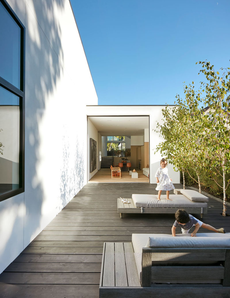 This modern house has a courtyard that features dark wood decking lined with trees and a couple of comfortable daybeds. #Courtyard #CourtyardDesign