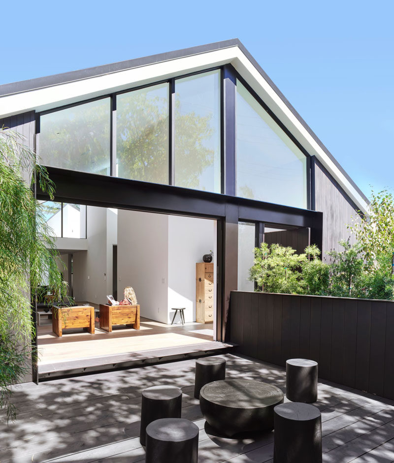 This modern house has a foyer that leads to the living room that features sliding glass doors that open to a private courtyard at the front of the home. #Courtyard #OutdoorSpace