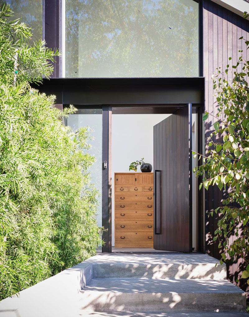 A pivoting dark wood front door welcomes visitors to this modern house. #FrontDoor #WoodFrontDoor #PivotingFrontDoor