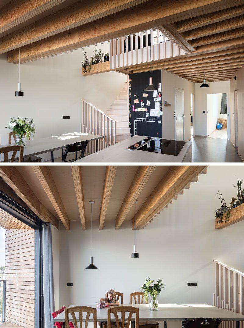Inside this modern house, there's an open plan kitchen and dining room, as well as a couple of bedrooms and the bathroom. Throughout the home, the structural wooden beams were kept visible as much as possible. #ModernHouse #HouseDesign #DiningRoom