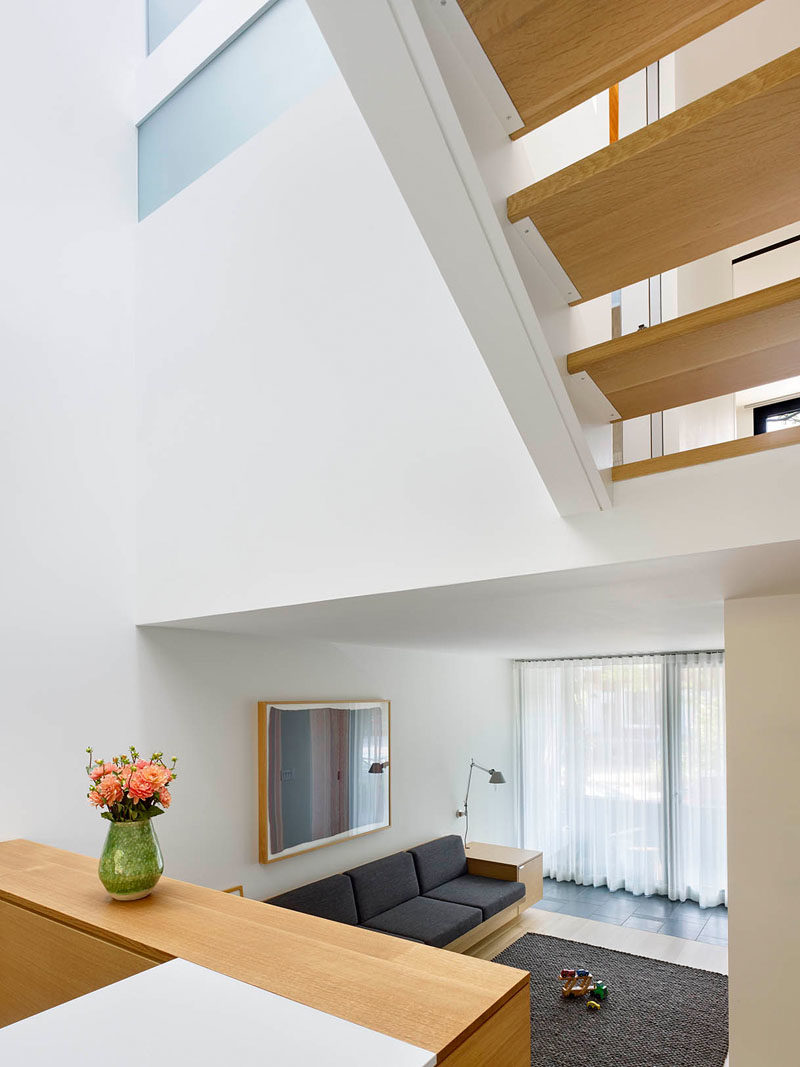This modern house has a split level-design, with the library sunken down from the kitchen and dining room. Both areas receive plenty of sunlight from the light well above. #Architecture #ModernHouse #Stairs #LightWell