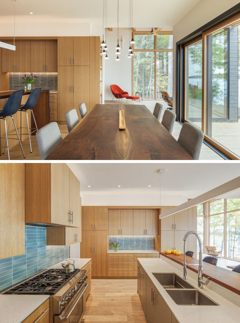 This modern lakeside house features large social spaces designed to host the extended family, with a spacious kitchen and dining room that connect to the screened porch by way of a large sliding door that pockets into the wall. #ModernDiningRoom #ModernKitchen #KitchenDesign #BlueTileBacksplash #WoodKitchen