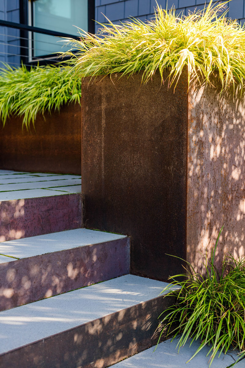 A concrete path with weathered steel planters filled with overflowing plants.