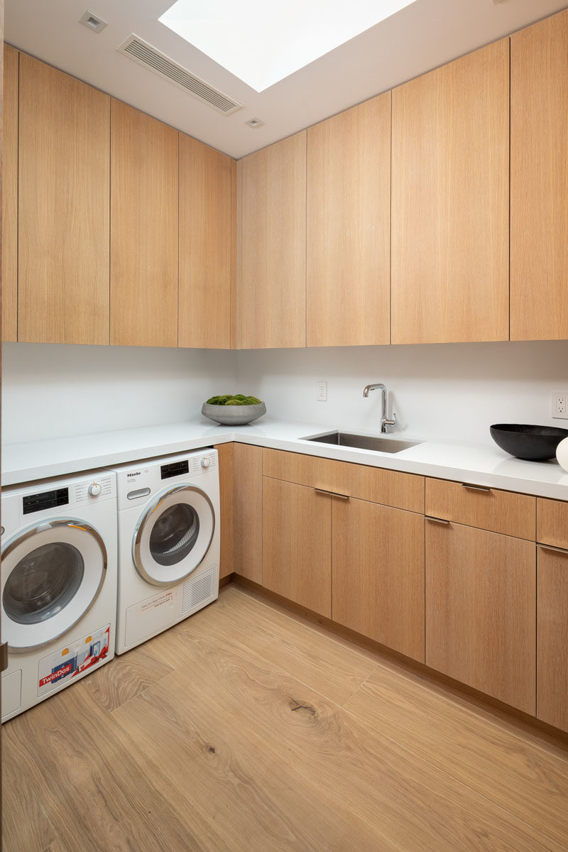 Laundry Room Ideas - This modern laundry room features floor-to-ceiling wood cabinets, a skylight, and plenty of counter space. #LaundryRoomIdeas #ModernLaundryRoom