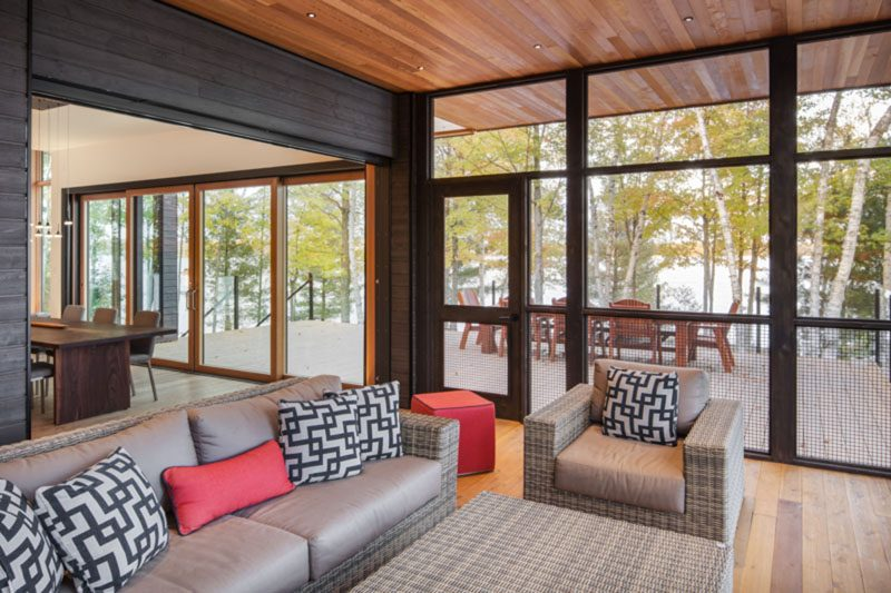 This modern lakeside house has a screened porch, and a large deck for outdoor entertaining. #ScreenedPorch #Deck #ModernLakesideHouse #ModernHouse #WoodCeiling