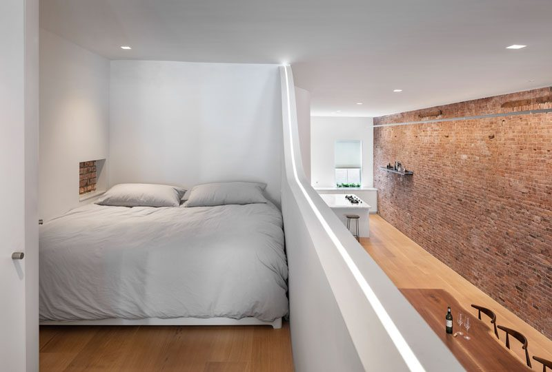This modern loft has a mezzanine that's home to a king size bed, and has a small shelving niche that acts as a bedside table. #Mezzanine #Loft #Apartment #Bedroom