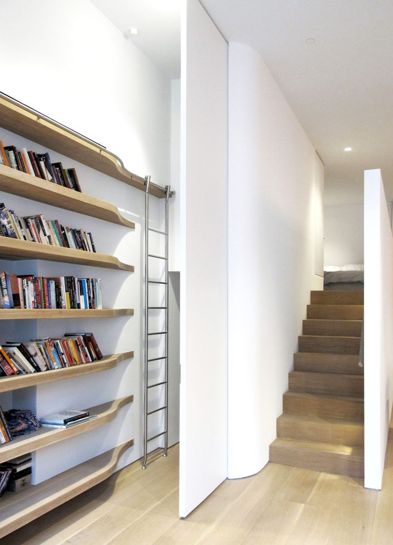 A custom stainless steel telescoping ladder and curving track follow the curving solid oak shelves and allow the ladder to be rolled out of sight behind a full height flush door to the laundry, storage, and mechanical room beneath the mezzanine. #ShelvingDesign #ShelvingIdeas #Stairs