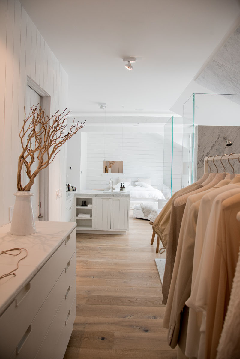 Bedroom Ideas - This master bedroom suite includes a sleeping area, an open bathroom, and a large walk-in closet. It uses light colors, glass, and natural light to keep it bright yet also relaxing. #MasterSuiteIdeas #MasterIdeas #ModernBedroom #BedroomIdeas #ModernBathroom #ModernWalkInCloset #ModernCloset