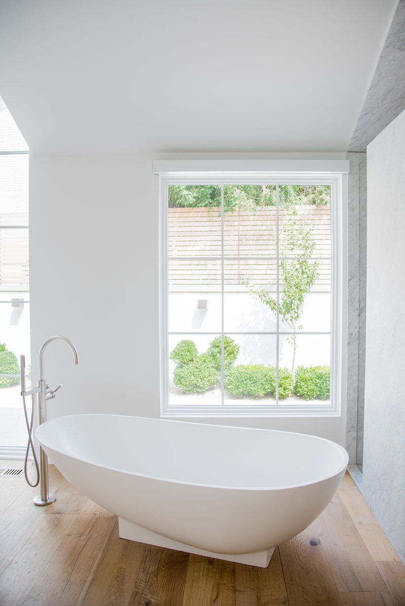 Bathroom Ideas - This modern master suite has a sculptural freestanding bathtub, that's also positioned to take in the garden views. #BathroomIdeas #FreestandingBathtub