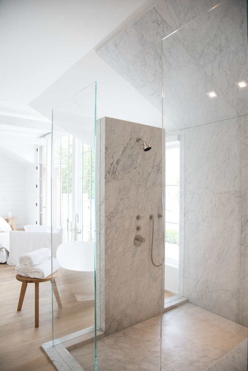 Bathroom Ideas - This modern bathroom that's open to the bedroom, features walls of glass and stone. #MasterSuite #ShowerIdeas #BathroomIdeas