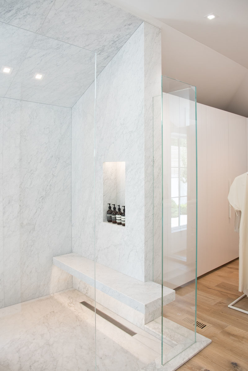 Bathroom Ideas - This modern glass enclosed shower features a built-in bench and shelf, both of which have hidden lighting to highlight the design details. #BathroomIdeas #ShowerIdeas #MasterBathroom