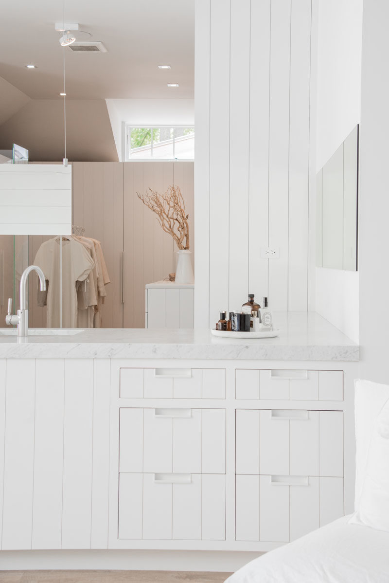 Bathroom Vanity Ideas - This modern master suite with an open bathroom and walk-in closet, has a custom-designed bathroom vanity with drawers that match the white panel cabinetry used throughout the space. #ModernBathroom #BathroomVanityIdeas #MasterSuite