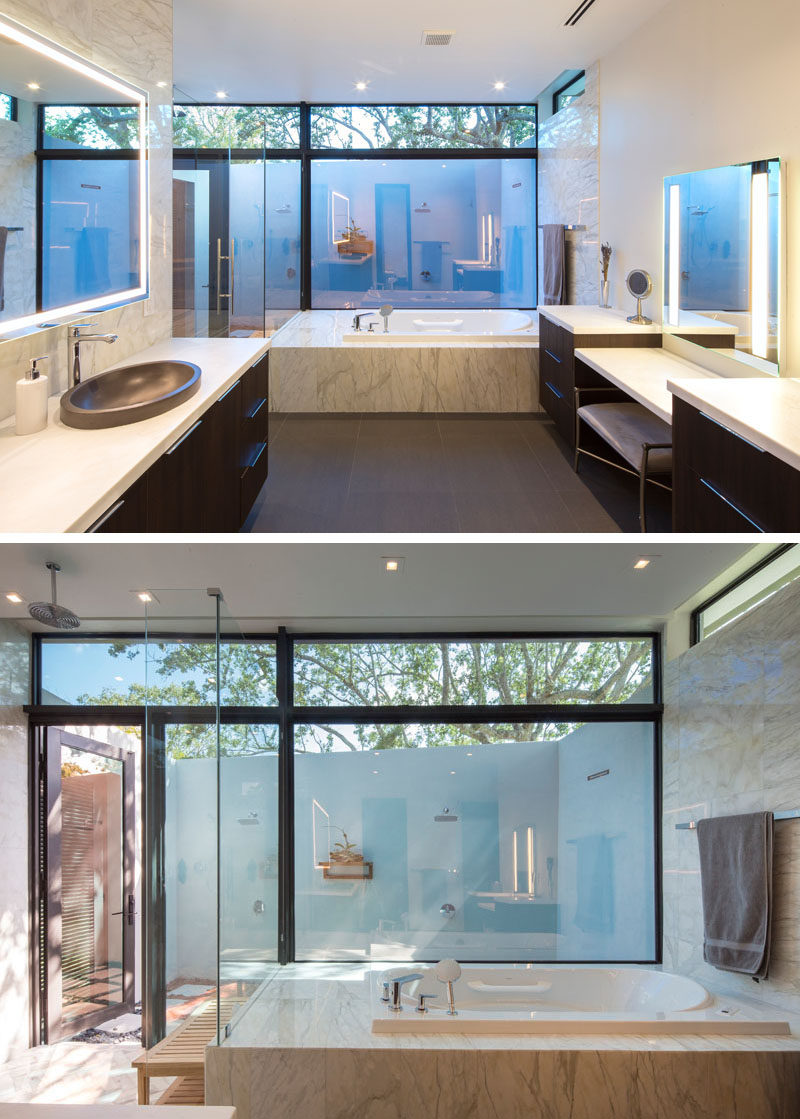 In this modern master bathroom, dark wood vanities provide a rich element to the space, while the built-in bath has views of the outdoor showers that are accessible via the interior shower. Carrara marble, mirrors with lighting, and large windows have been used to keep the bathroom bright. #BathroomIdeas #MasterBathroom #OutdoorShower #BuiltInBathtub #WoodVanity