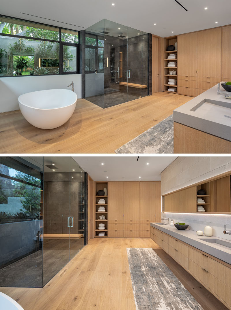 Bathroom Ideas - This modern en-suite bathroom has a sculptural freestanding white bathtub, a glass enclosed shower for two, windows with a view of the plants outside, and wood cabinetry. #BathroomIdeas #BathroomDesign #ModernBathroom