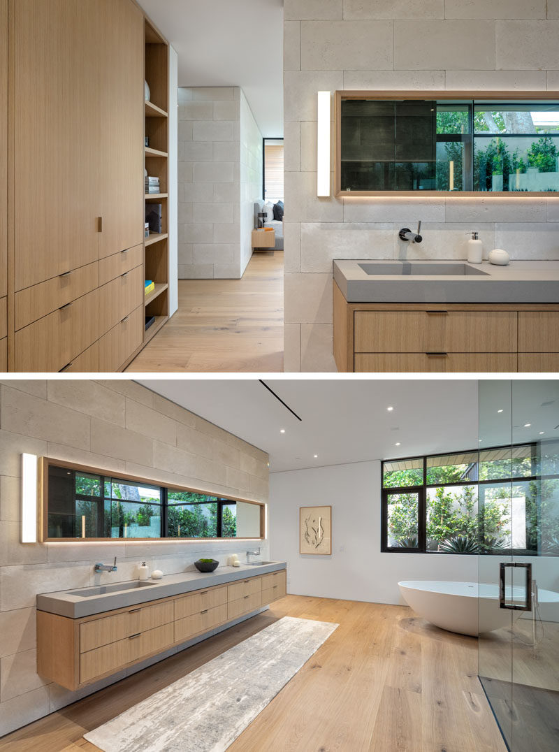 Bathroom Ideas - In this modern bedroom, a long floating wood vanity sits below a mirror with hidden lighting, and has a thick grey counter with built-in sinks. #BathroomVanity #VanityIdeas #BathroomIdeas #ModernBathroom