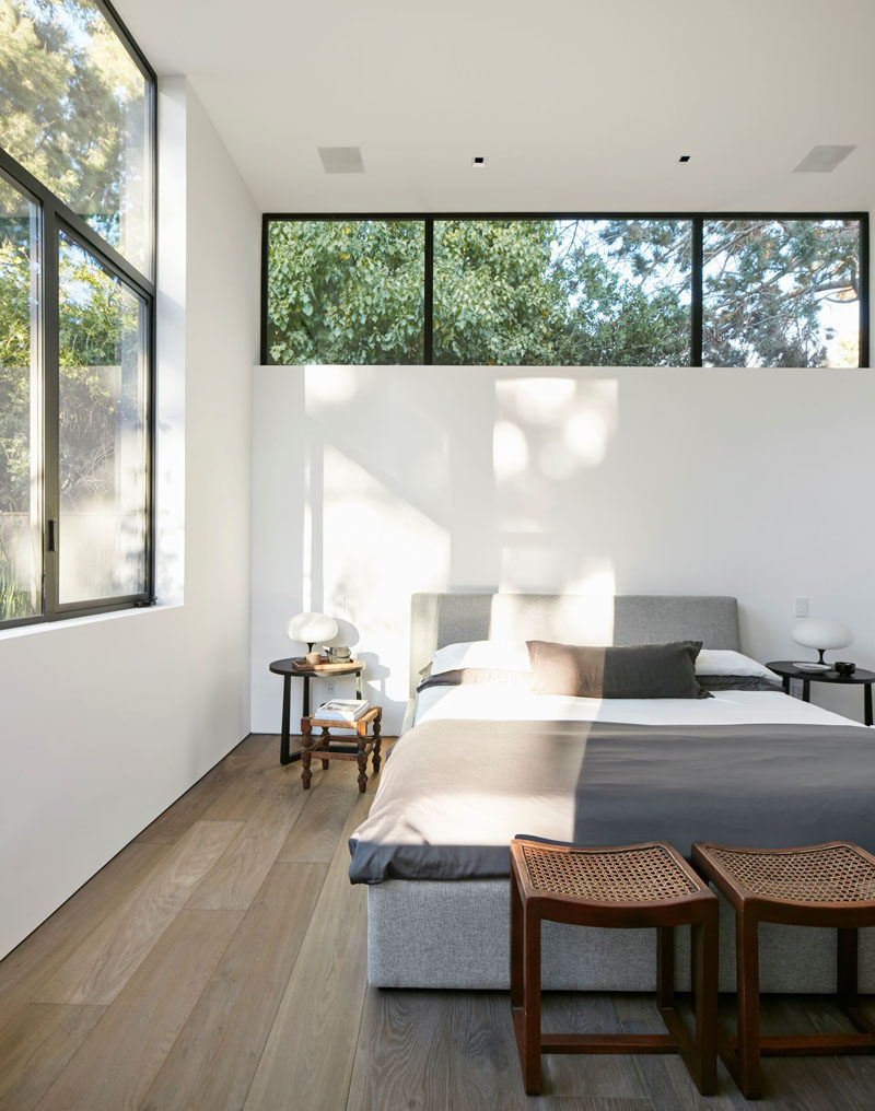 This modern master bedroom has a row of windows above the bed, with a second set of windows adding to the amount of the natural light the room receives. #ModernBedroom #BedroomDesign