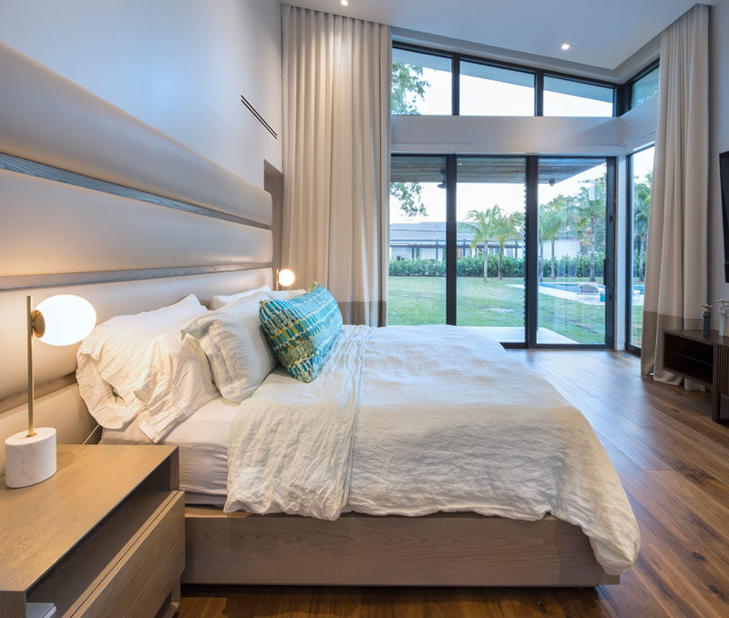 In this modern master bedroom, sliding glass doors open to the backyard, while a custom bed design incorporates bedside tables and a leather headboard. #MasterBedroomIdeas #ModernBedroom #BedroomDesign
