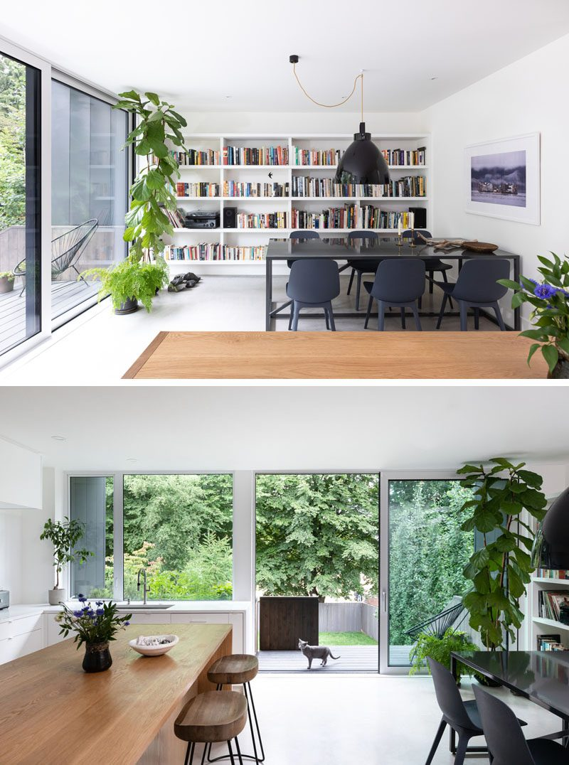 This modern open plan dining room has dark furnishings that contrast the bright white walls, while a shelving unit is filled with colorful books. A sliding glass door opens the room to the backyard where there's a deck and a lawn surrounded by trees. #DiningRoomIdeas #Bookshelf #SlidingGlassDoor