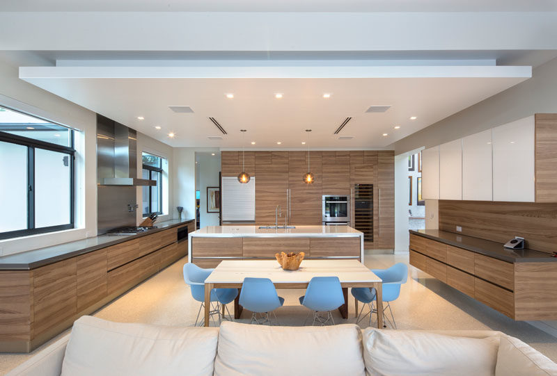 This large modern kitchen with wood cabinets shares the space with the dining area. #KitchenDesign #WoodKitchen