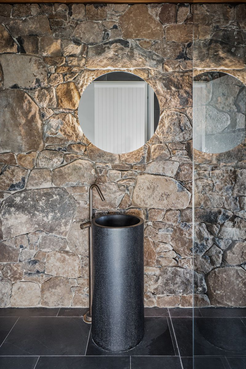 In this modern bathroom, the stone wall creates a backdrop for the minimalist black pedestal sink, while the backlit round mirror adds a soft glow to the space. #StoneWall #ModernBathroom #RoundMirror #BacklitMirror #BathroomIdeas