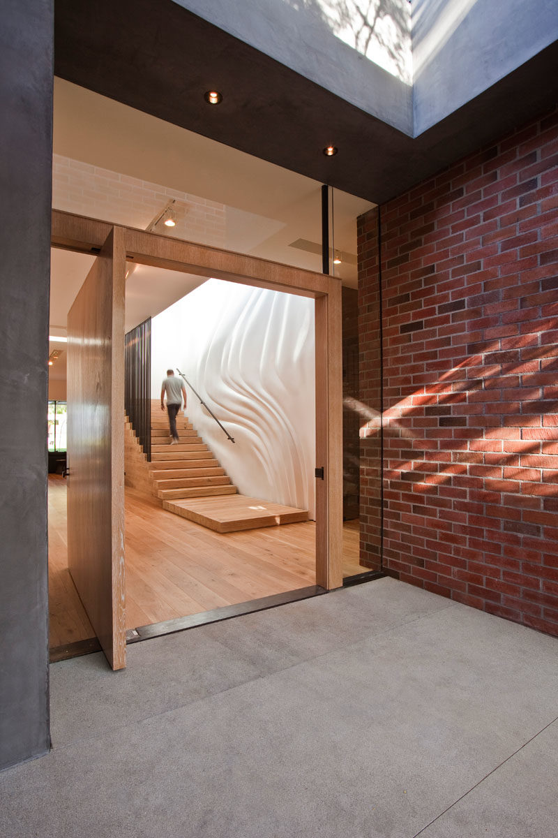 Stair Ideas - This modern house has a custom designed rough-sawn lumber staircase with a rippling and custom-molded wall that gives the illusion of a fabric curtain blowing in the wind. #ModernStairs #WoodStaircase #SculpturalWall