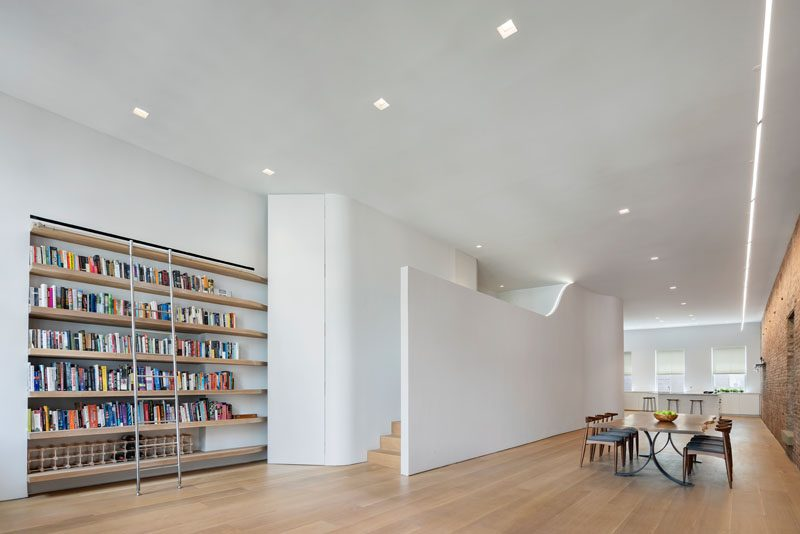 At the other end of this modern loft, there's a wall of solid oak library shelves near some stairs that lead up to a mezzanine that features a LED Light that lines the open wall. #ModernShelves #LoftApartment #ApartmentDesign
