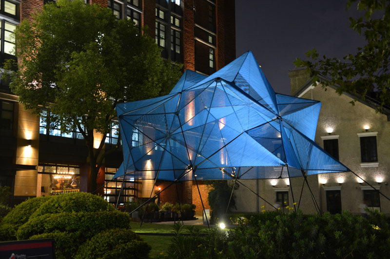 This modern public art installation named 'Cobalt Muffin', has a geometric shape that floats over a lawn, with the design made from 60 similar triangles, that have been covered with a semi-transparent skin made from more than 4 miles (7.5 km) of elastic ropes, creating a vibrant addition to the area. #ModernArt #ArtInstallation #PublicSculpture