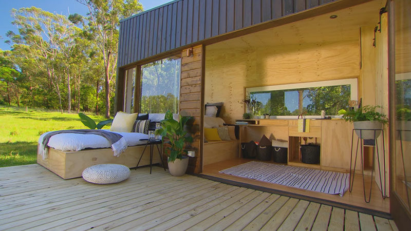 TIny House Ideas - This tiny house, which measures in at just 19 feet x 7 feet  (6m x 2.4m), has a simple modern design that covered in cypress pine cladding. Two siding doors were used to create the large picture window on the end of the house, while a large pivoting glass door opens the interior to the deck. #TinyHouseIdeas #ModernTinyHouse #TinyHouseDesign