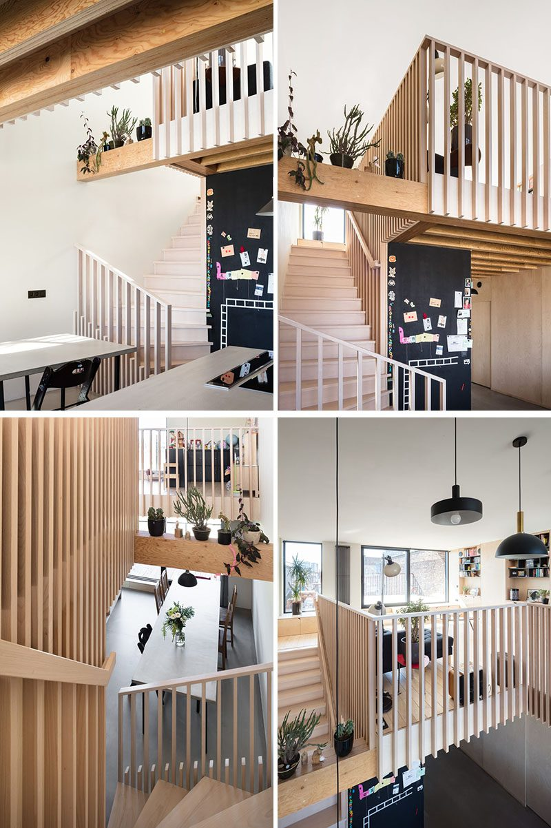 Stairs beside a black chalkboard wall lead up to the upper floor of this modern house. Wooden slats were used for the handrails and parapet and serve as a guideline throughout the house. #WoodStairs #ModernStairs #StairDesign