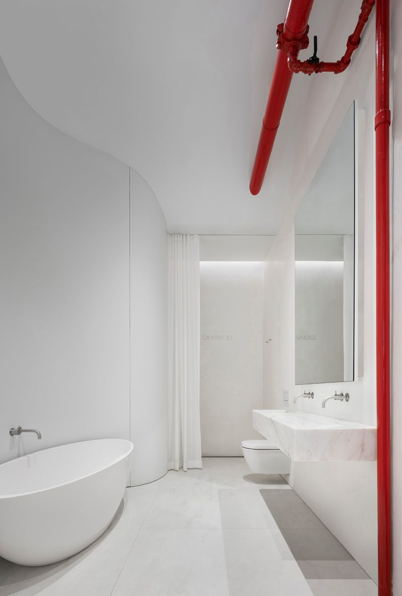 This modern bathroom includes ten foot long floor slabs of pale porcelain tile, white Imperial Danby stone for a cantilevered sink, and waterproof plaster walls. The old sprinkler main valve adds a bright pop of color to the white interior, while concealed rollers enable a large mirrored door to slide smoothly to the side, revealing a large cabinet with a soft LED light. #BathroomDesign #MinimalistBathroom #BathroomIdeas #WhiteBathroom