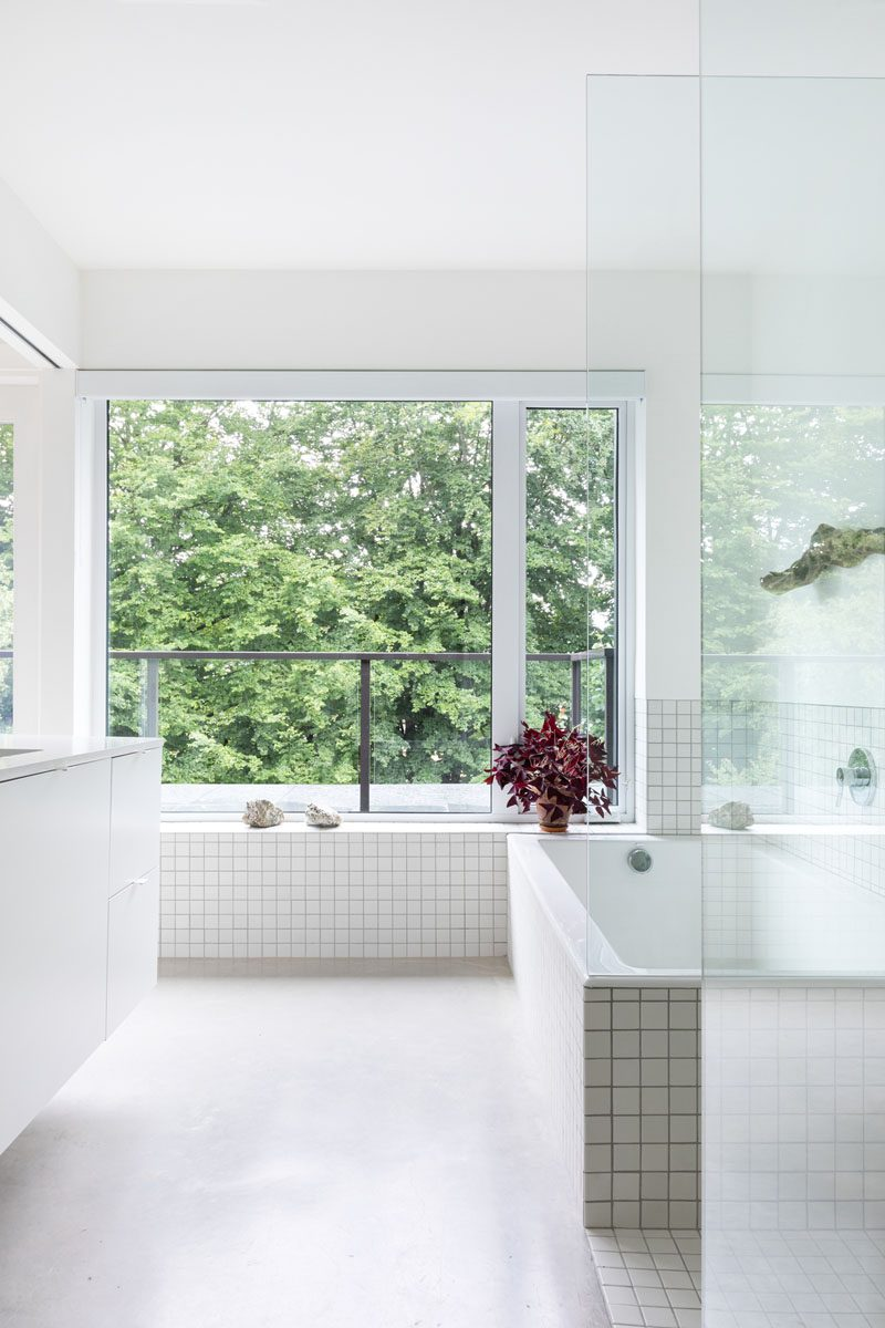 In this modern bathroom, large windows look out to the trees, while a built-in bathtub is surrounded by white square tiles, and is adjacent to a glass enclosed shower. #ModenBathroom #WhiteBathroom #BuiltInBathtub #ConcreteFloors
