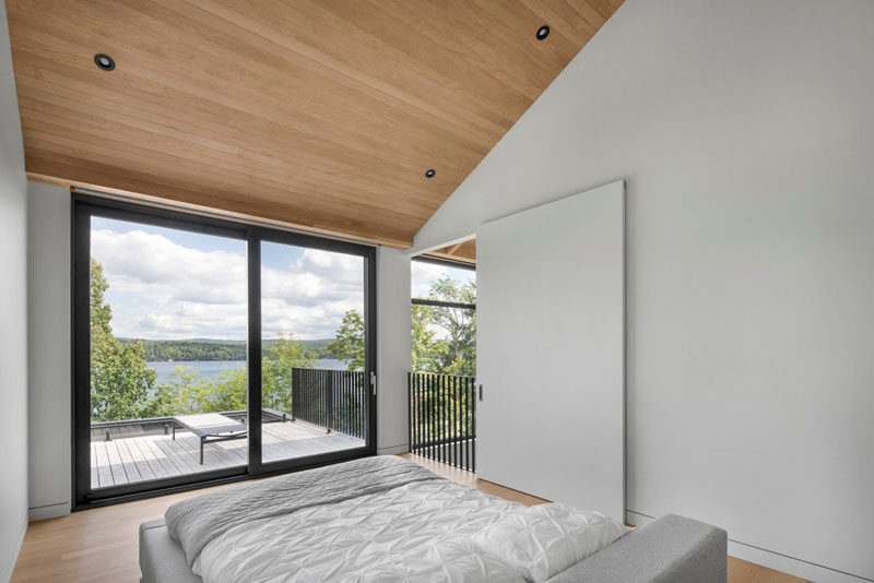 This modern bedroom has been furnished minimally, allowing the tree and water views to be the main focus. #MinimalBedroom #BedroomDesign