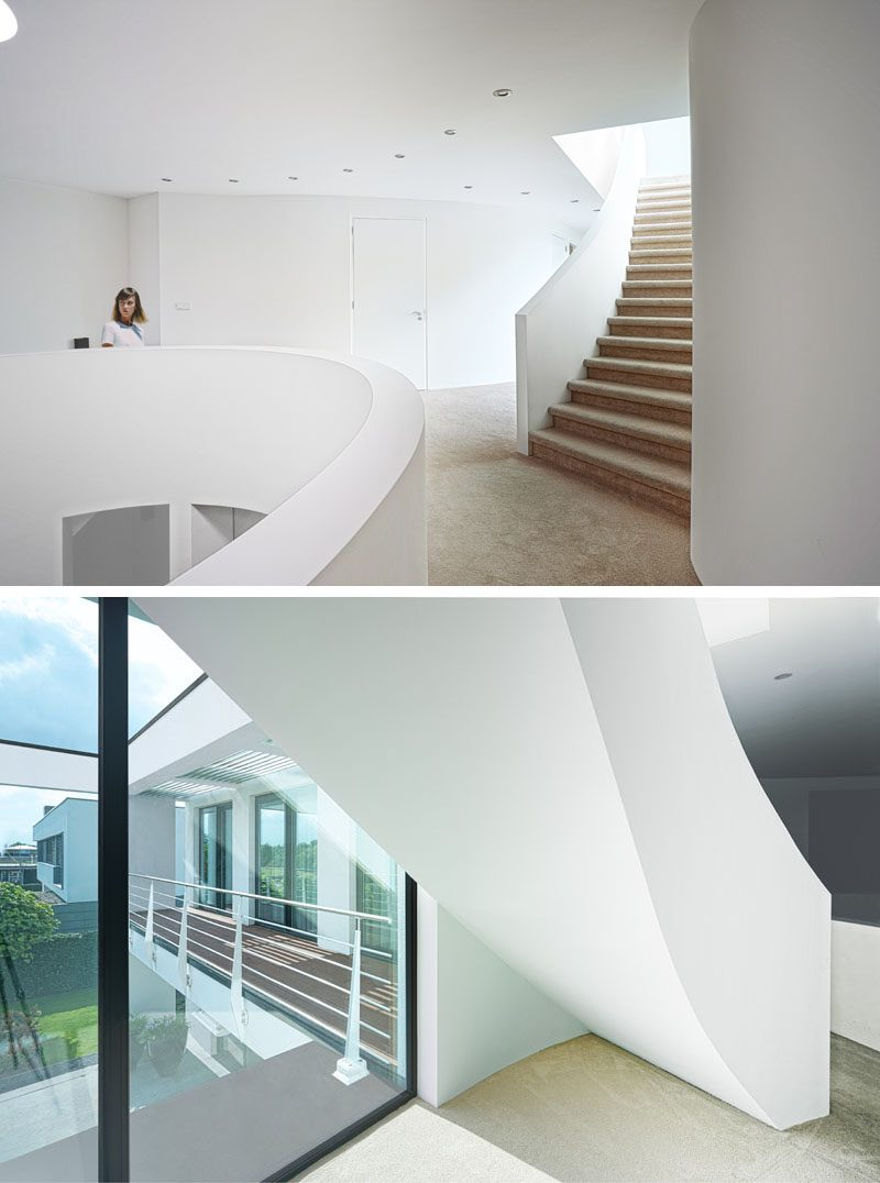 The interior of this house has been kept minimal with bright white walls, while curving stairs add a sculptural element and connect the various levels of the house. #Staircase #CurvingStairs #SculpturalStairs