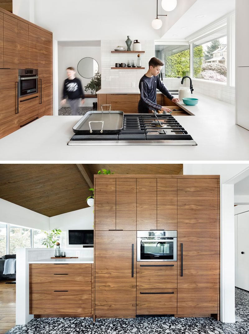 This remodeled kitchen has a bright and modern appearance with a large peninsula, wood cabinets, and a dining area with banquette seating. #ModernKitchen #WhiteKitchen #WoodKithen #KitchenDesign