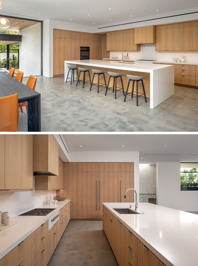 Kitchen Ideas - This modern gourmet kitchen has minimalist wood cabinets, an integrated fridge, a large white island with seating, and a walk-in pantry. #ModernKitchen #KitchenIdeas #WoodKitchen #WhiteCountertops