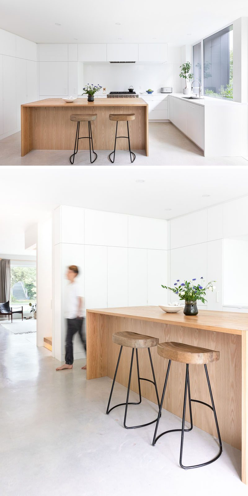 This modern kitchen brings nature inside with the use of a wood island, while white countertops and minimalist hardware free cabinets blend seamlessly into the white walls. #WhiteKitchen #WoodKitchenIsland #ModernKitchen #MinimalistWhiteCabinets