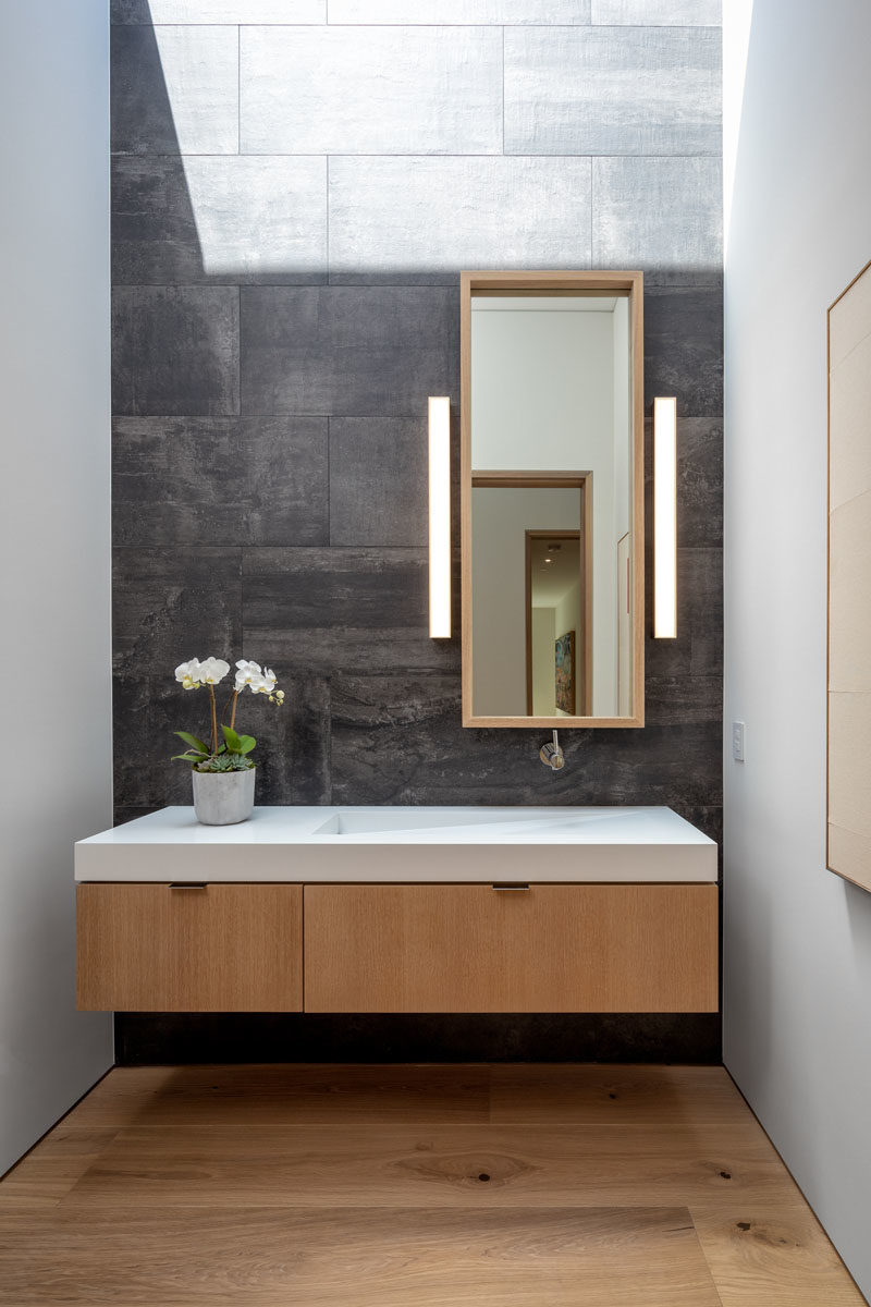 Vanity Ideas - In this modern bathroom, grey tiles provide a backdrop for the floating wood vanity, that features a sink integrated into the countertop. #BathroomIdeas #BathroomVanity #ModernBathroom