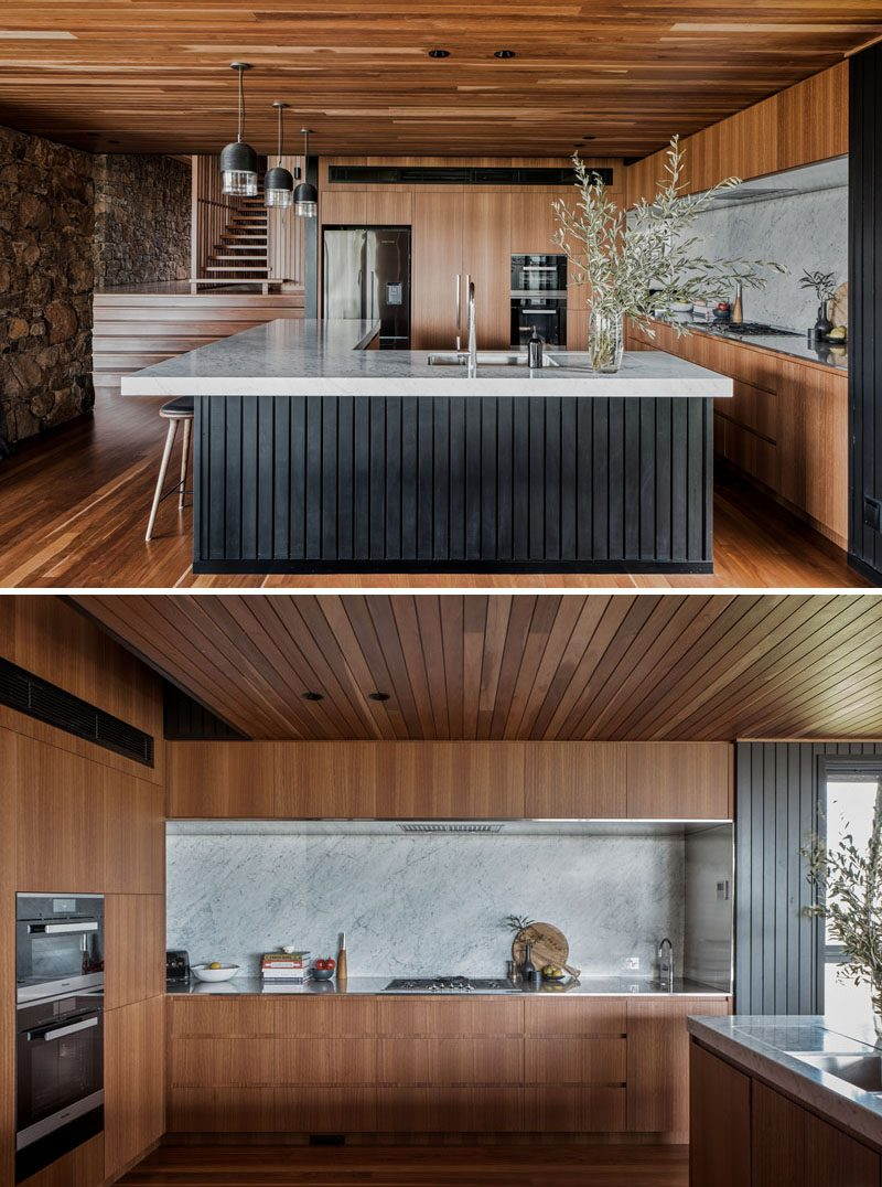 In this modern kitchen, a large L-shaped island with an overhanging countertop provides creates a place for the family to gather while cooking. #KitchenDesign #ModernKitchen #LShapedKitchenIsland #KitchenIslandDesign