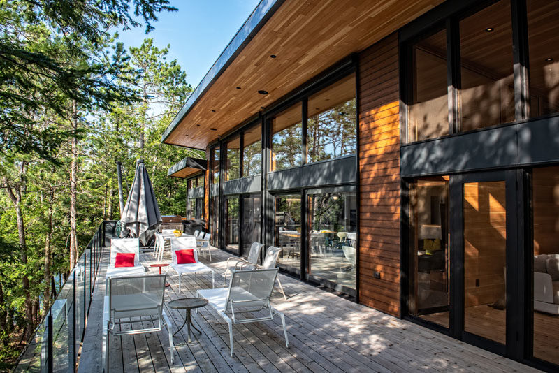 This modern cottage has a pair of oversized patio doors with retractable screens allows the interior spaces to open to the outdoors during the summer and provides natural ventilation. #ModernCottage #Architecture #ModernHouse