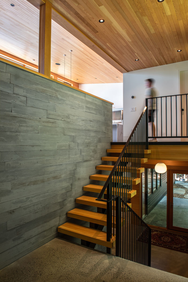 Stair Ideas - Throughout the house, polished concrete floors provide both thermal mass and durability, while Douglas fir windows and ceilings add warmth to the interior. Wood and metal stairs lead to the main living spaces on the upper level of the home. #WoodStairs #ModernStairs #PolishedConcreteFloors #ConcreteWall #DouglasFir #WoodCeiling