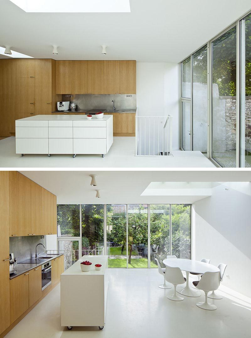 People often use materials that contrast kitchen cabinets when designing a kitchen island, and a portable kitchen island is no different. In this example, the designers decided to create the movable kitchen island using white as the featured color. This not only stands out from the wood cabinets, but it also complements the white walls, stair handrail, and the dining furniture. #PortableKitchenIsland #MovableKitchenIsland #KitchenIslandOnWheels #KitchenDesign
