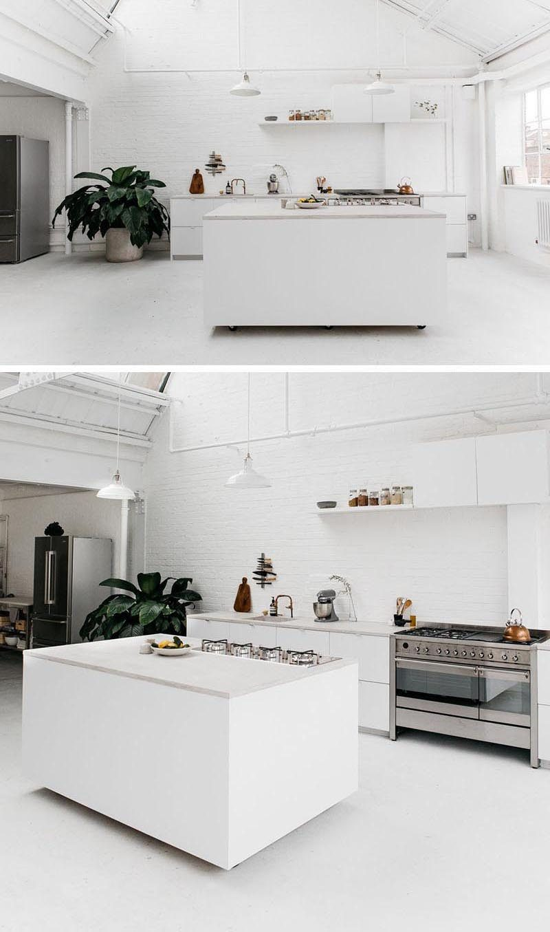 In this bright white modern kitchen, the custom designed portable kitchen island has it's wheels somewhat hidden from view, creating the illusion of it floating above the ground. #PortableKitchenIsland #MovableKitchenIsland #KitchenIslandOnWheels #KitchenDesign