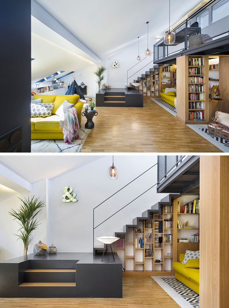 In this modern attic, stairs provide separation between the living room and a small library area that features shelving that neatly fits beneath the stairs and mezzanine. #AtticRenovation #ModernAttic #AtticDesign