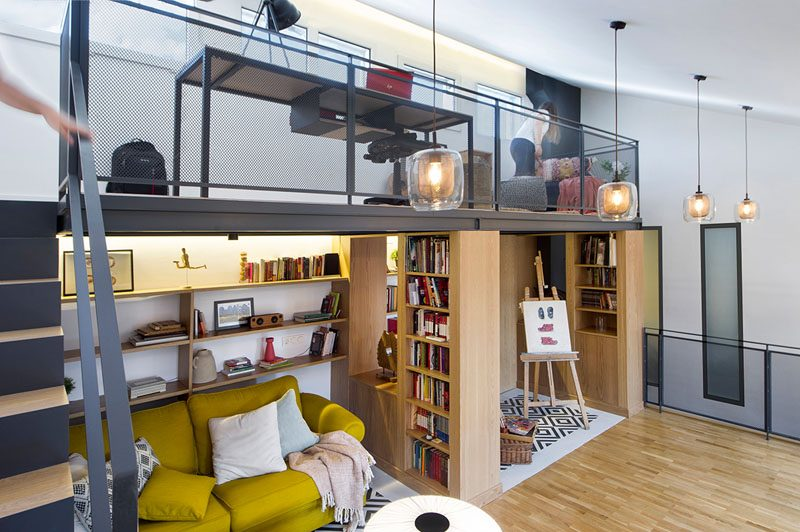 This modern attic has a mezzanine that's been furnished with a desk and sitting area, making it an idea space for homework or an office. #ModernAttic #Mezzanine #HomeOffice #Library