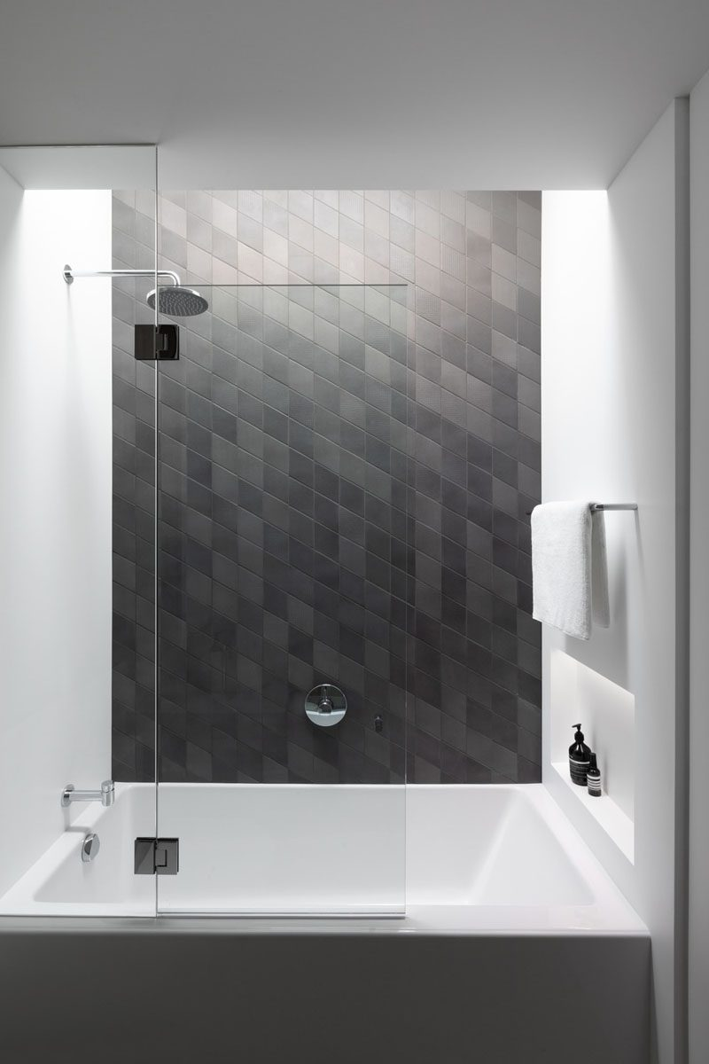 This modern grey bathroom features a shower niche that can be accessed from the shower and the bath. #ShowerNicheIdeas #ShowerNiche #ModernBathroom #BathroomDesign #BathroomIdeas