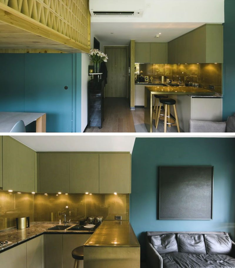 This small apartment that features a lofted sleeping area above the dining room, a metallic kitchen, and bold blue accent walls. #LoftedBedroom #LoftBedroom #SmallApartment #ApartmentDesign #TinyApartment