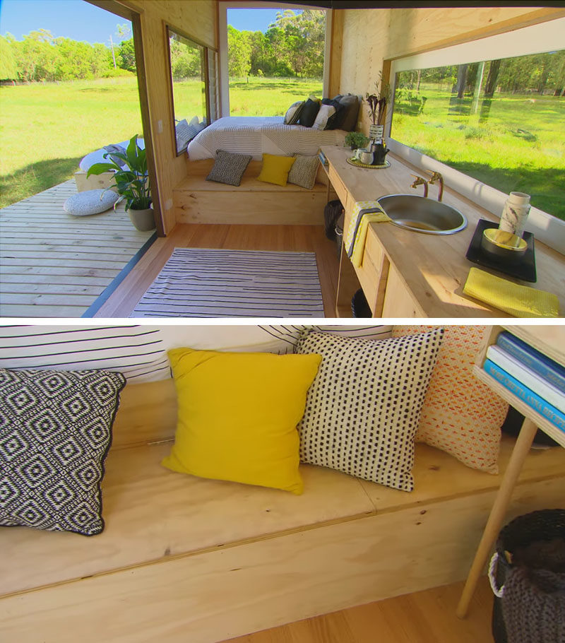 Tiny House Ideas - Inside this modern tiny house, there's a raised bed at one end, that takes advantage of the window views. A small bench that doubles as a step, also provides additional storage. #TinyHouseIdeas #ModernTinyHouse #TinyHouseBedroom #TinyHouseStorage